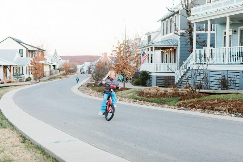 girl riding a bike up street
