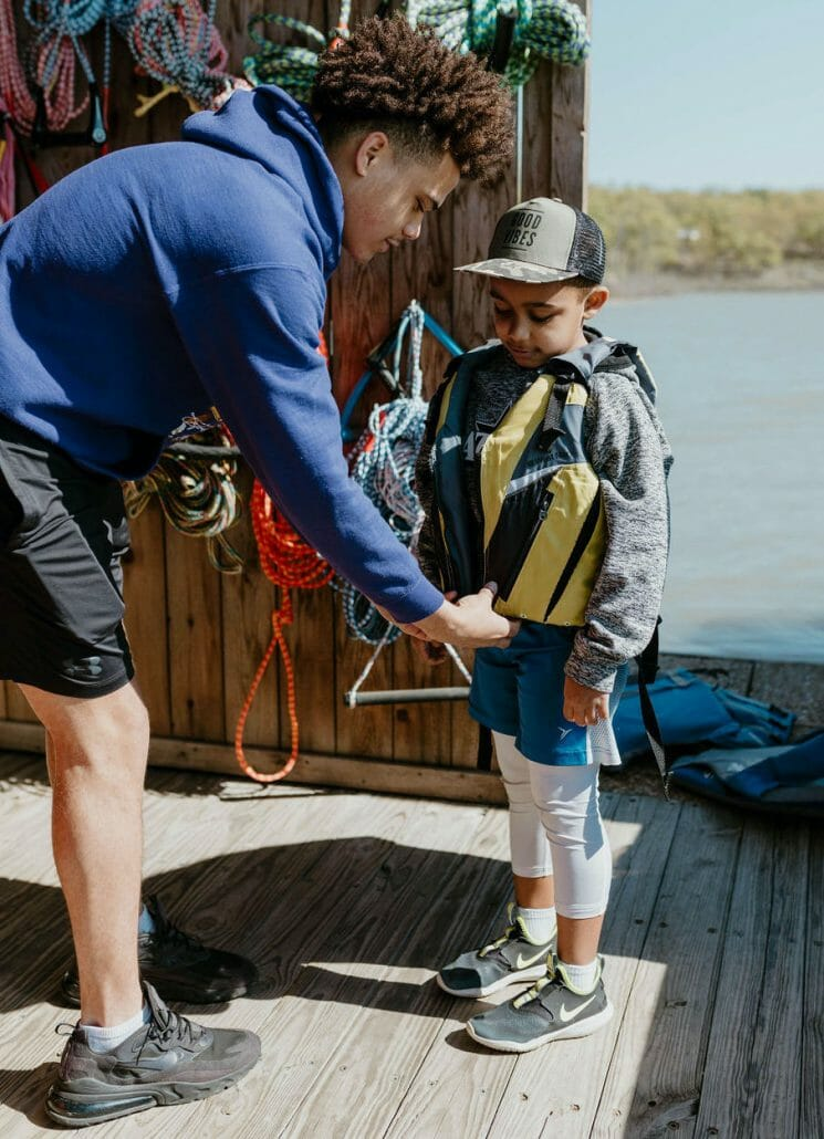 Boat Club helping kid with lifejacket